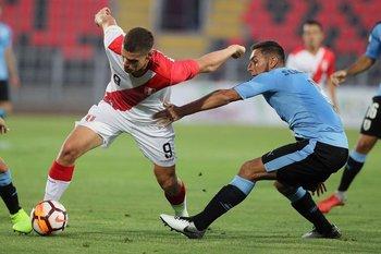 Sebastián Cáceres intenta frenar a un rival