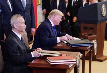 Donald Trump y el viceprimer ministro chino Liu He firmando el acuerdo.