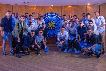 El plantel de futbolistas junto al nuevo escudo