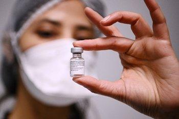 Una trabajadora de la salud sostiene una dosis de la vacuna de Pfizer/BioNTech