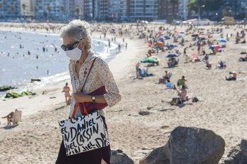 Una mujer mayor camina por los alrededores de la playa