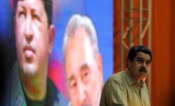 Nicolás Maduro delante de un poster con la imagen de Hugo Chávez y Fidel Castro