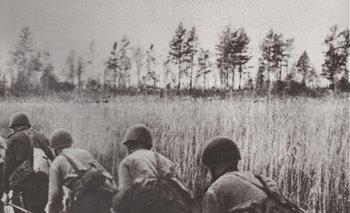 Soldados soviéticos cruzan un bañado sobre un estrecho puente de troncos en el verano de 1944, en su ofensiva sobre Finlandia
