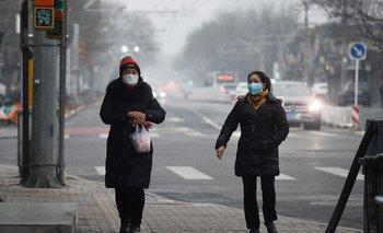 Dos mujeres con tapabocas caminan por Beijing