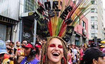 """Una de las participantes del carnaval lleva un tocado decorado con la frase """"amor y resistencia"""""""