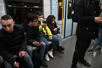 Transeúntes usan tapabocas en el metro de Milán.