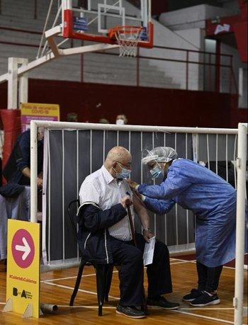 Un trabajador de la salud es vacunado contra el covid-19 en Argentina