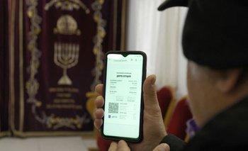 """Un judío practicante muestra su """"pasaporte verde"""" –que certifica que está vacunado contra el coronavirus– en una sinagoga de Isreael"""