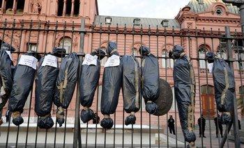 Los congregados colgaron enormes bolsas mortuarias negras con nombres de dirigentes oficialistas vacunados.