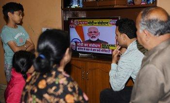 Una familia india mira en televisión el anuncio del primer ministro, Narendra Modi, sobre la cuarentena general