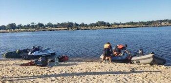 Hay dos gomones, una moto de agua y un equipo de buceo trabajando en la búsqueda