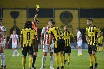 Andrés Cunha le muestra la tarjeta amarilla a Giovanni González ante River y el futbolista queda automáticamente suspendido para jugar ante Montevideo City Torque