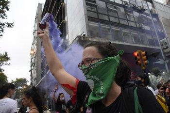 Una mujer deja salir humo violenta durante la marcha del 8 de marzo