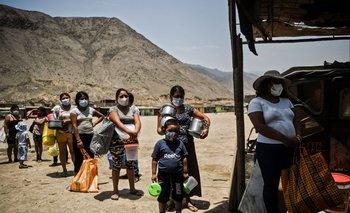 Personas mantienen distancia de seguridad mientras esperan recibir alimentos en un comedor de beneficencia en Comas, en las afueras del norte de Lima, en medio de la pandemia de coronavirus