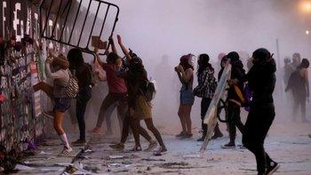 Las mujeres intentan derribar el muro que protege a la sede de gobierno ern Ciudad de México