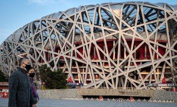 Ciudadanos chinos caminan cerca del estadio Nido de Pájaro