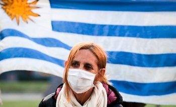 Una mujer protegida con tapabocas se ve frente a una bandera de Uruguay en Montevideo