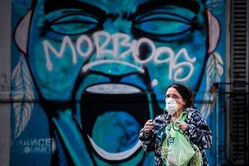 Una mujer con tapabocas camina en una jornada de la cuarentena obligatoria a causa del covid-19 en la ciudad de Buenos Aires