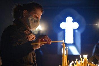 Una mujer cristiana enciende velas durante la Pascua