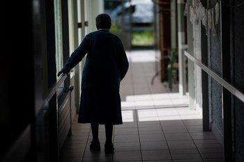 Anciana camina por el pasillo de un geriátrico