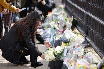 Una mujer entrega flores en el Palacio de Buckingham