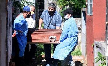 Trabajadores cargan el ataúd de una víctima del covid-19 en el cementerio Cementerio del Sur de Asunción
