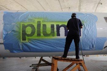 Trabajadores de la aerolínea Pluna borran el logo de los aviones Bombardier que comprados en el sistema de leasing que serán devueltos al banco en Canadá - 2012. Deslizá para ver la galería.