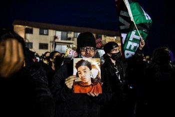 Un manifestante sostiene el retrato de Daunte Wright durante la séptima noche de protestas por la muerte a tiros de Daunte Wright a manos de un oficial de policía en Brooklyn Center.