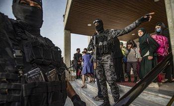 Los miembros de las fuerzas de seguridad kurdas sirias se mueven entre sí mientras niños salen de un edificio en la sede de la Departamento de Relaciones Exteriores, en el noreste de Siria