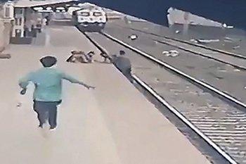Fragmento del video en el que un hombre rescata a un niño que cae sobre las vías del tren en una estación de India