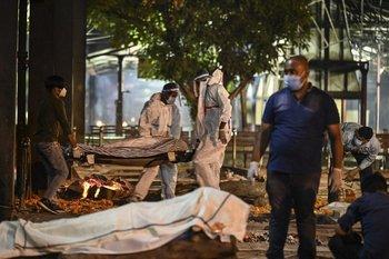 Los familiares y el personal médico llevan el cadáver de una víctima del covid-19 en el crematorio Nigambodh Ghat, a orillas del río Yamuna en Nueva Delhi.