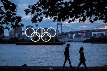 Una vista general muestra los anillos olímpicos iluminados al anochecer en el paseo marítimo de Odaiba en Tokio