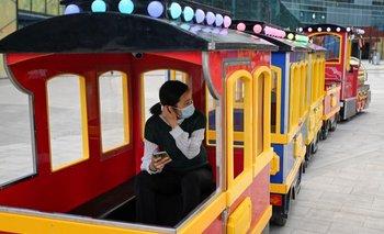 Mujer con barbijo pasea en un tren infantil en China
