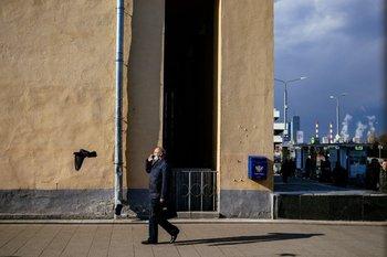 Un hombre habla por celular mientras camina por Moscú, en un día soleado