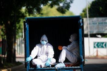 Dos hombres con el equipo de protección médica recorren las calles de India