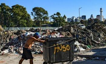 Un hombre empuja un contenedor en una villa de Buenos Aires, Argentina