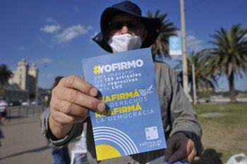 Un hombre enseña un folleto a favor de la campaña de recolección de firmas contra la LUC