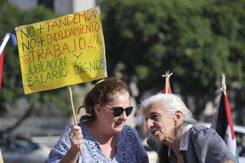 Dos señoras asisten a un acto por el Día de los Trabajadores frente al Palacio Legislativo