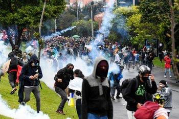 Manifestantes chocan con la policía antidisturbios durante una protesta contra un proyecto de reforma tributaria frente a la casa del presidente colombiano