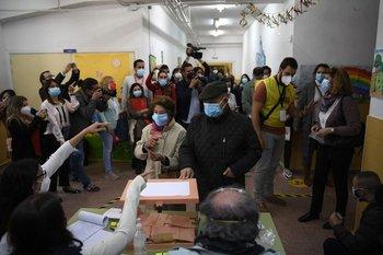 Una pareja de adultos mayores emitiendo sus votos en un colegio electoral en Madrid durante las elecciones regionales del 4 de mayo de 2021.