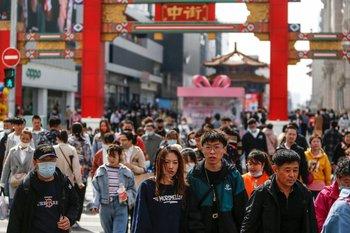Personas visitando una calle comercial en Shenyang, China.