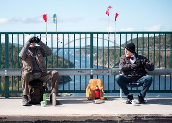 Pontus Berglund (L) looks at birds into his binoculars as he sits on the Swedish side while his brother Ola sits on the Norwegian side of the old bridge of Svinesund and the new Svinesund Bridge is seen in the background, in Svinesund, Norway and Sweden, on May 1, 2021. They haven