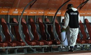 Un funcionario desinfectando el sector de los suplentes de un estadio