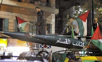 """Hombres desfilan con un modelo de cohete escrito en árabe, """"Brigadas Qassam"""" (brazo armado de Hamas) durante una manifestación convocada por el grupo islamista palestino Hamas en la ciudad de Saida"""
