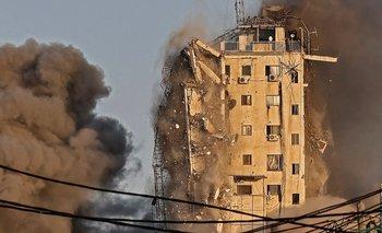 El humo se eleva desde la torre Al-Sharouk mientras se derrumba después de ser golpeada por un ataque aéreo israelí, en Gaza