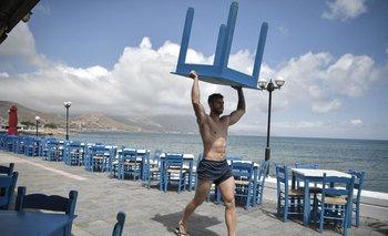 Un empleado poniendo en orden las mesas en un restaurante de Kísamos, en Creta