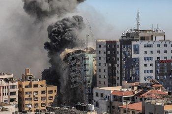 Una columna de humo asciende de una torre de 14 plantas en la ciudad de Gaza, sede de la agencia de noticias estadounidense AP, la cadena de noticias Al Jazeera y otros medios internacionales