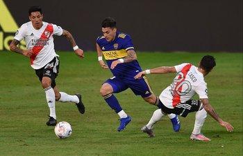 Cristian Pavón pasa entre Enzo Pérez y Milton Casco