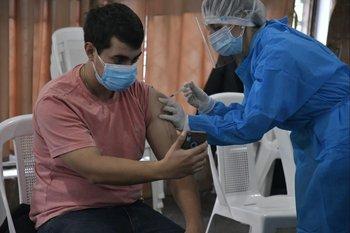 Un joven se saca una selfie mientras recibe la vacuna
