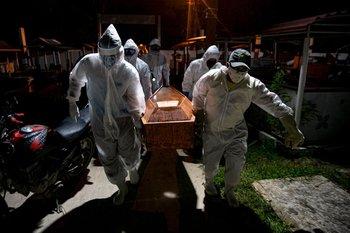 Trabajadores trasladan a una víctima del coronavirus en Brasil